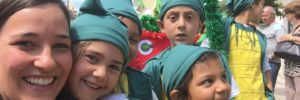 Eine Freiwillige hat Spaß mit kostümierten Kindern.