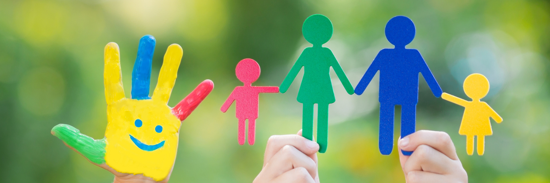 Buntbemalte Kinderhand und zwei Hände die eine Familie aus gestanztem bunten Papier halten.