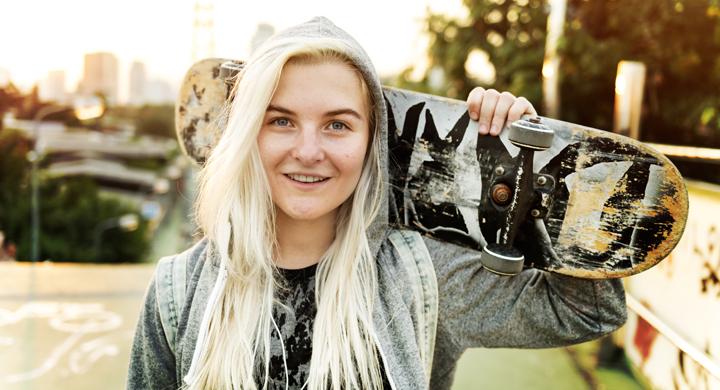 Blondes Mädchen mit Hoodie und Skateboard in der Hand