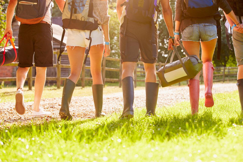 Beine von Jugendlichen, sie laufen mit Gummistiefeln durchs Gras
