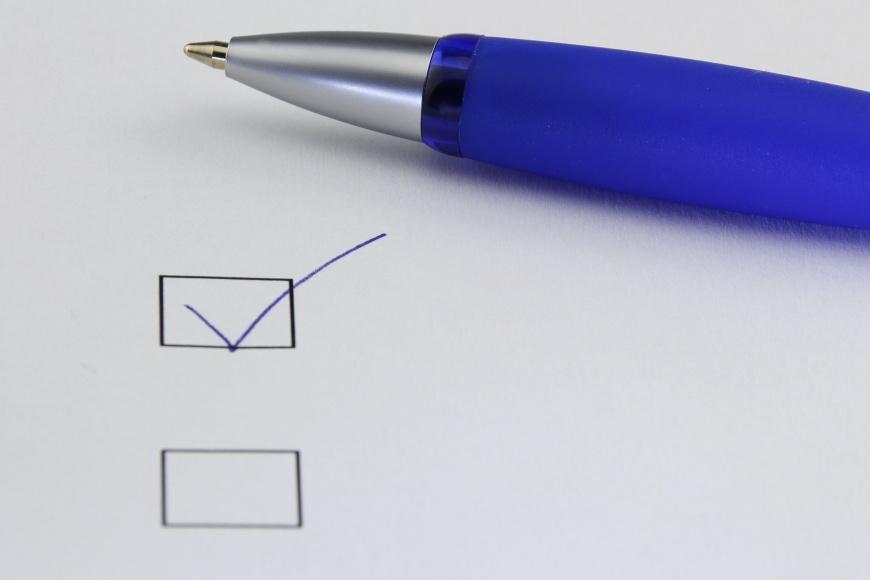 Papierblatt auf dem ein Kugelschrieber und eine Checkbox abgehakt ist.