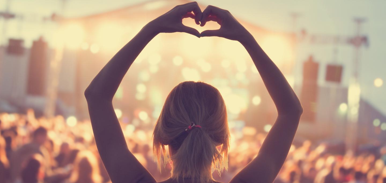 Mädchen von Hinten, sie steht vor einer Bühne und formt ein Herz mit ihren Händen