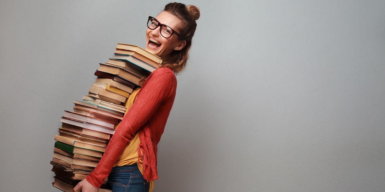 Junges Mädchen fröhlich mit ganz vielen Büchern am Tragen