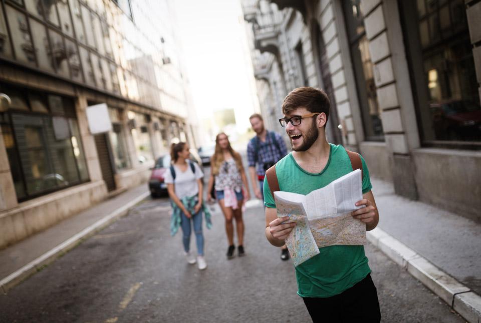 Jugendlicher mit Stadtkarte in der Hand im Urlaub