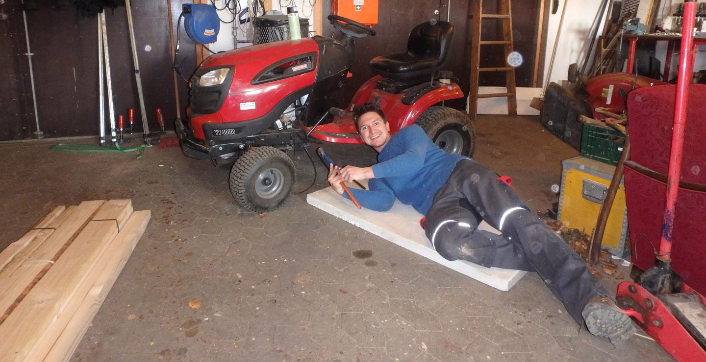 Jugendlicher repariert einen Traktorrasenmäher