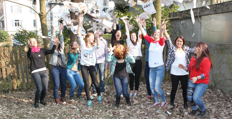 Eine Gruppe von Jugendlichen wirft Papier in die Luft.