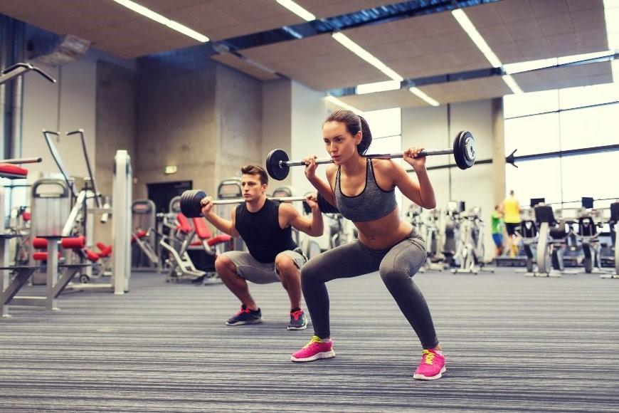 Junge Frau und junger Mann trainieren im Fitnesscenter