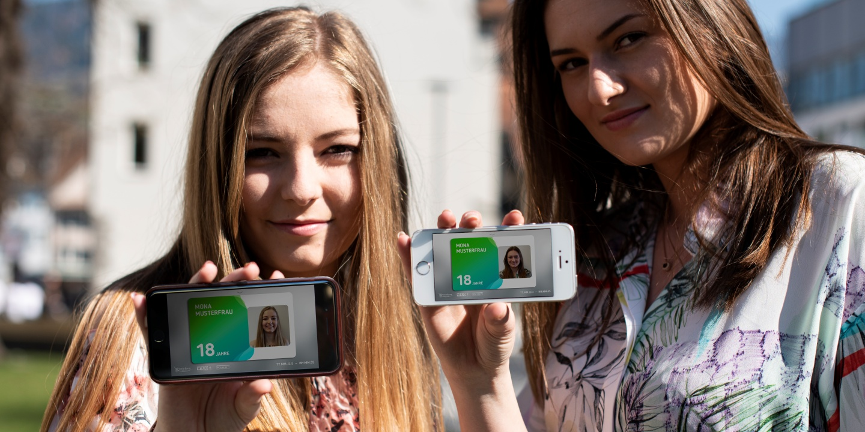 zwei junge Frauen, die die aha-App herzeigen.