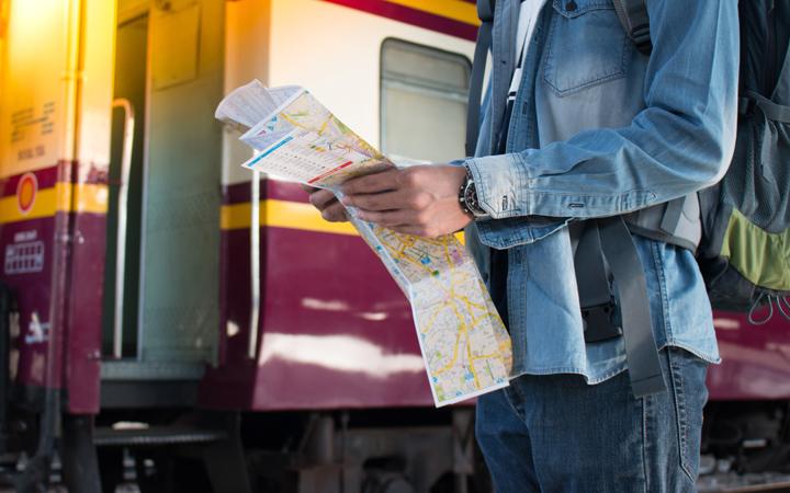 Jguendlicher steht mit einer Landkarte vor einem Zugwaggon.