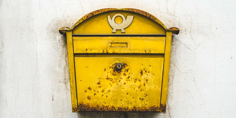 Gelber rostiger Briefkasten an einer Wand.