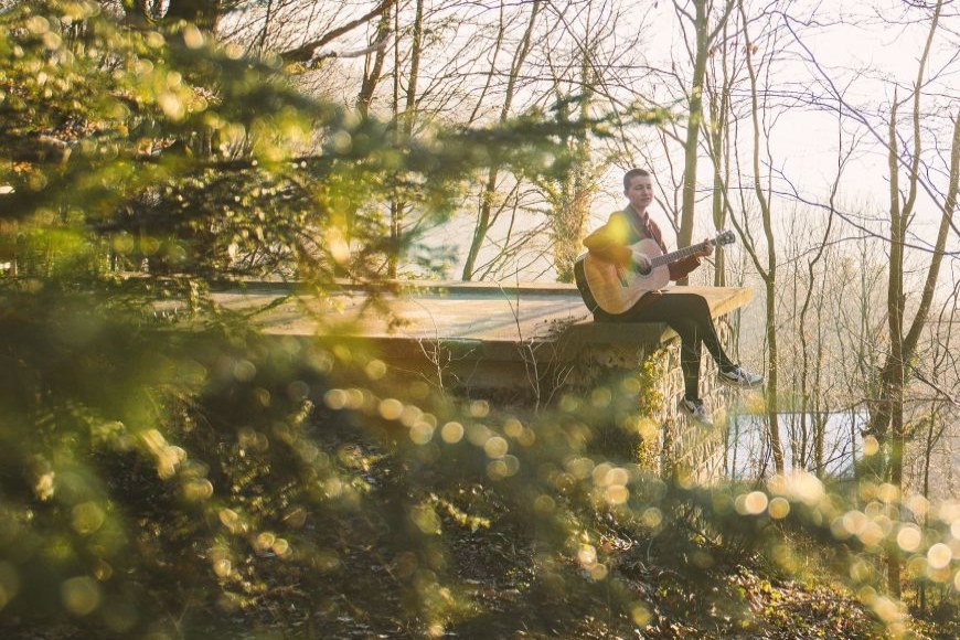 Junge Frau sitzt im Wald und spielt Gitarre