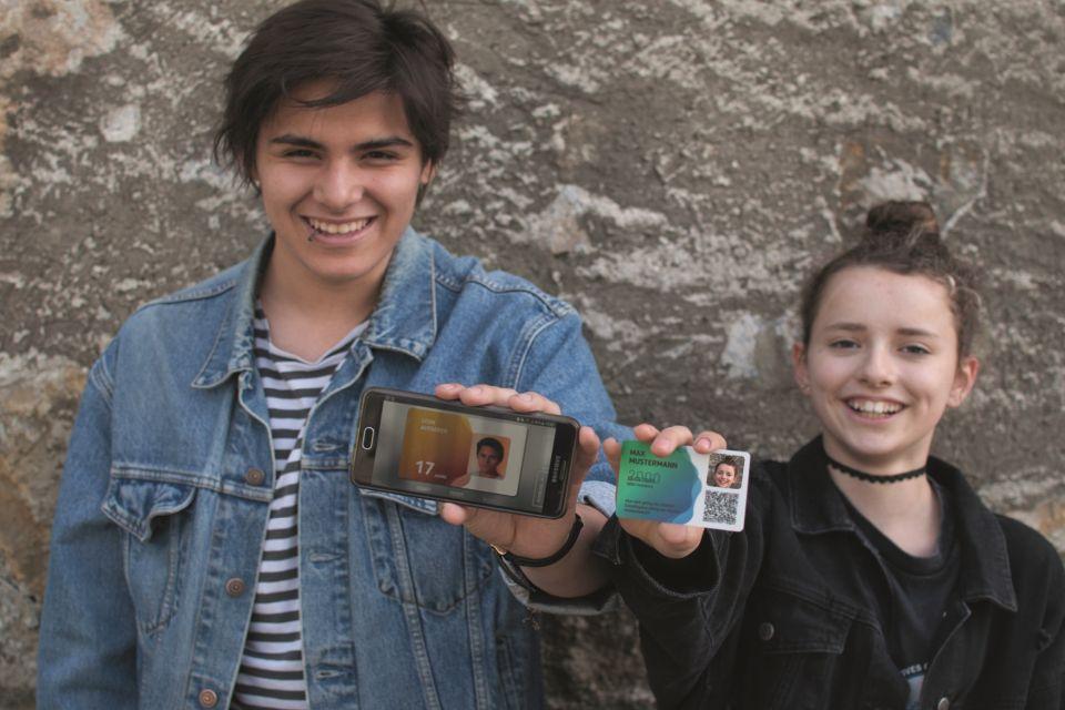 Zwei Jugendliche stehen an der Wand und halten ihre aha cards ins Bild. Der Bursche zeigt seine aha card in der App. Das Mädchen zeigt ihre aha Plastikkarte.