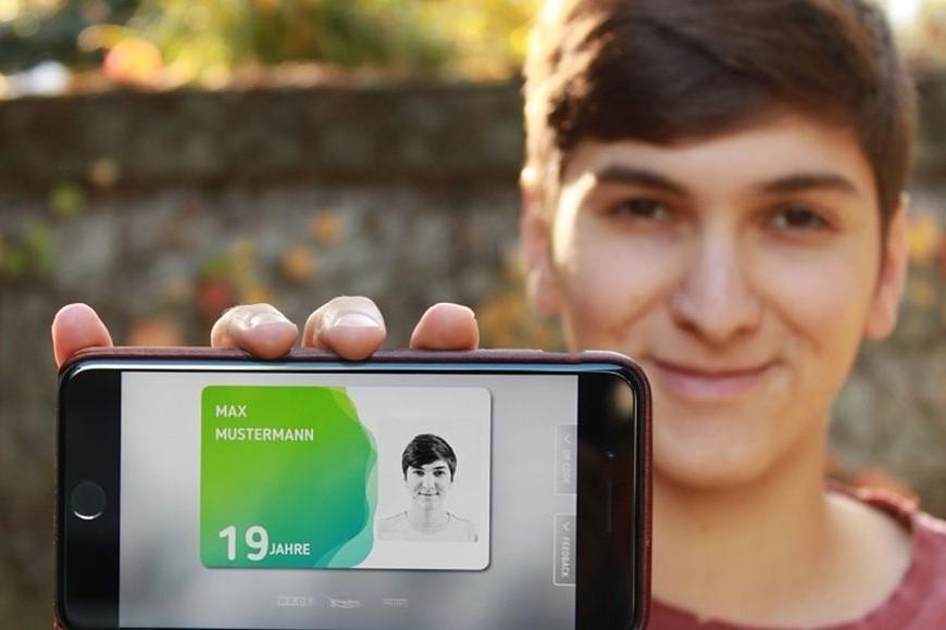 Junger Bursch zeigt seine aha card im App auf seinem Handy