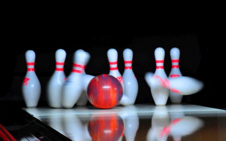 Bowling-Pins werden von einer Bowlingkugel getroffen