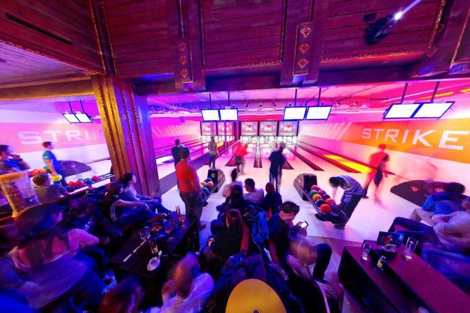 In einer bunt beleuchteten Bowlinghalle sind rund 20 Menschen versammelt und spielen Bowling