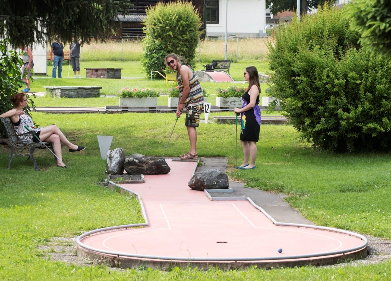Junger Mann spielt Minigolf.