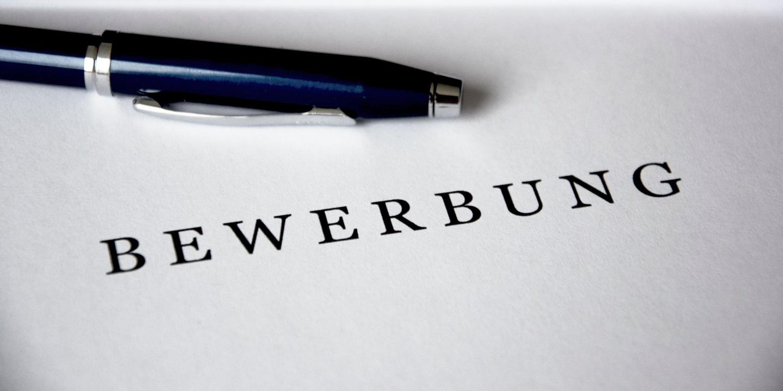 Füllfeder auf einem weißen Blatt Papier auf dem Bewerbung steht.