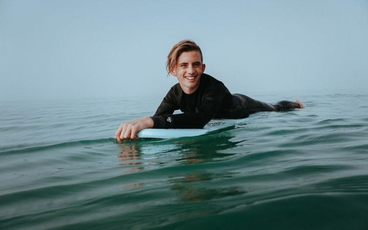 Juendlicher auf einem Surfbrett im Wasser