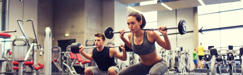Junger Mann und junge Frauen trainieren im Fitnesscenter