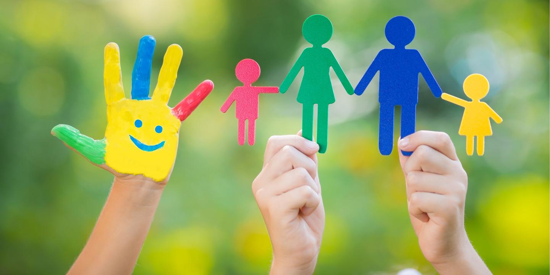 Angemalte Kinderhand und Papierfiguren für Familienmitglieder.
