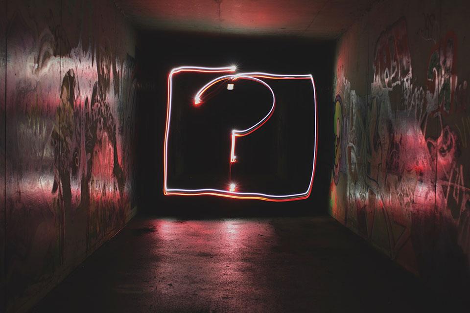 Neonfragezeichen in einem dunklen raum