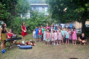 Bildbeschreibung: Ein Kinderchor steht unter einen Baum in einem Garten und singt. Rechts vom Chor steht eine junge Frau mit rotem Kleid. Links vom Chor ist ein junger Mann in der Hocke. Gegenüber steht ein Keyboard auf dem ein Jugendlicher spielt. Eine Jugendliche steht daneben und blättert die Noten um. Neben dem Keyboard liegt ein Geigenkoffer auf dem Boden und verschiedene Trommeln.