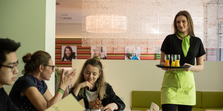 Jugendliche kellnert in einem Lokal.
