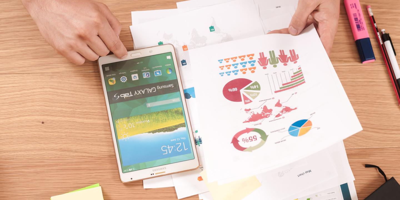 Smartphone mit Papieren auf denen Diagramme zu sehen sind.