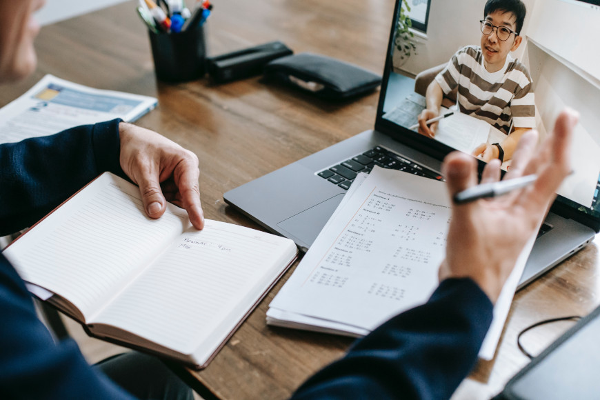 Online-Nachhilfe vor einem Laptop in dem man einen Jugendlichen sieht.
