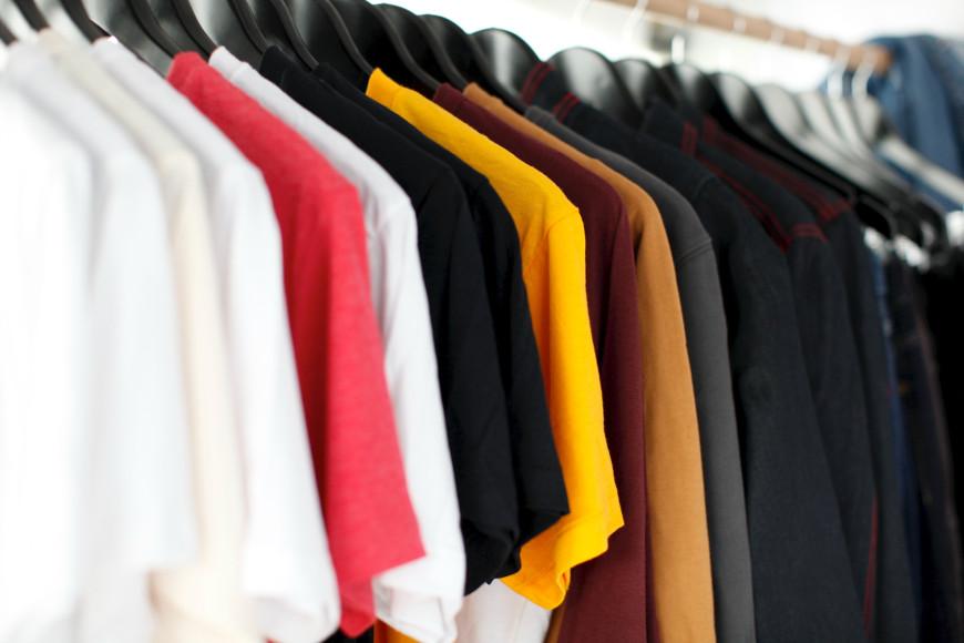verschiedenfarbige T-Shirts aufgehängt in einer Reihe.