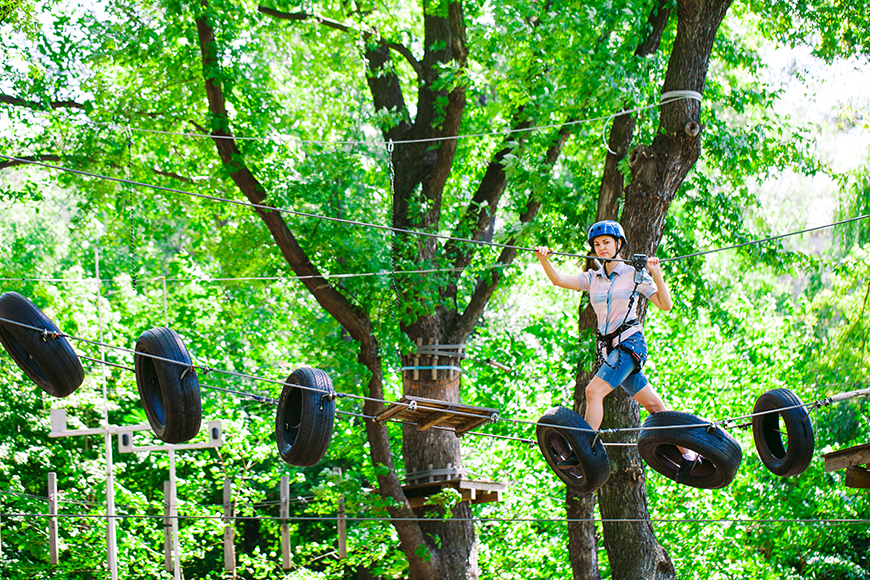 Jugendliche in einem Klettergarten die über Reifen läuft.
