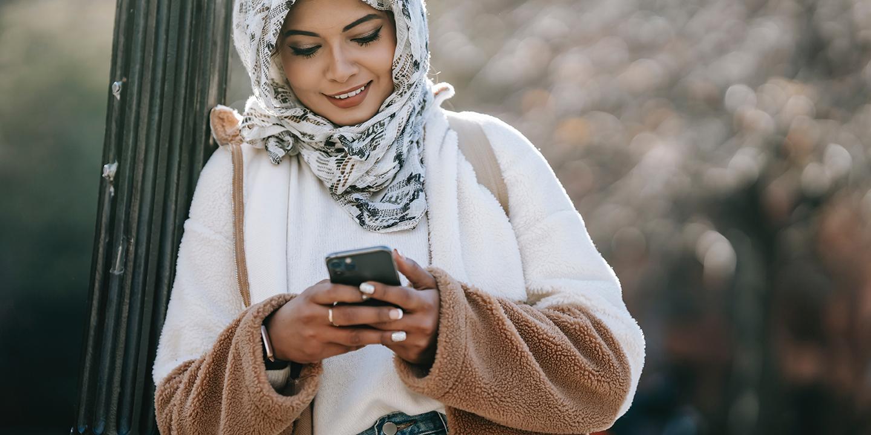 Eine junge Frau schaut in ihr Smartphone und lächelt.